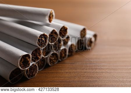 Pile Of Cigarettes On Wooden Table, Closeup