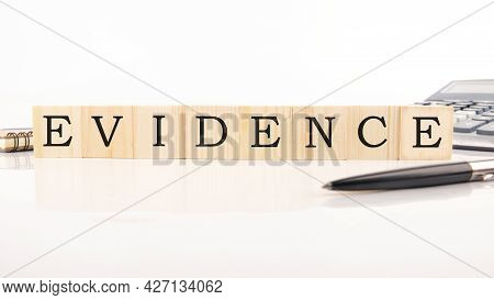 Words Evidence On Wooden Cubes On White Background Next To Calculator, Pen, Notepad