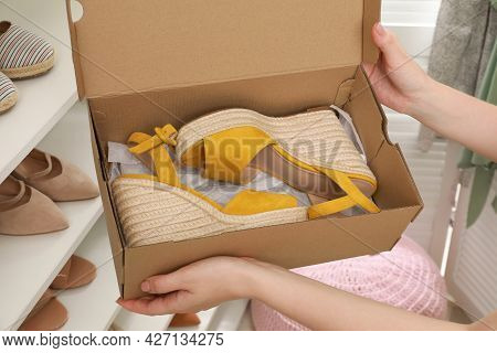 Woman Holding Box With Wedge Shoes Near Rack Indoors, Closeup