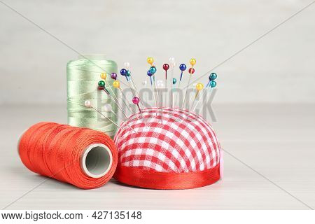 Pin Cushion And Coils Of Threads On Light Beige Table