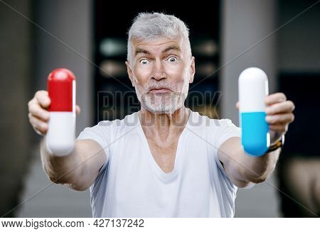 Emotional Handsome Gray Haired Senior Man With A Big Red And Blue Pill In His Hand. Medicine And Hea