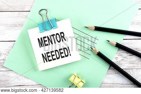 Text Mentor Needed On The Short Note With Pencils On Wooden Background
