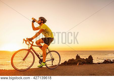 Triathlon race biking cycling sports athlete cyclist man drinking water bottle while riding road bike at sunset after training wearing cycle accessories, smartwatch, helmet, sunglasses, gloves, shoes.