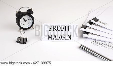 Card With Text Profit Margin On A White Background, Near Office Supplies And Alarm Clock. Business
