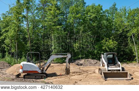A Mini Excavator And Compact Front Loader Sits On The Dirt At A New Home Construction Lot, With Tree