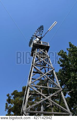 A Metal Wind Mill Is On A Wooden Frame. It Is Seen From Below Against A Blue Sky, Surrounded By Gree
