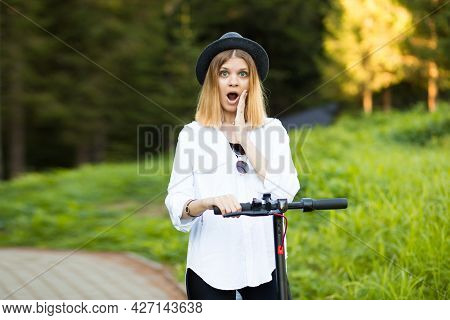 Trendy Carefree Woman With A Surprised Expression In White Shirt And Black Hat Ride On Kick Scooter