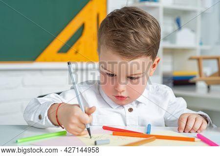Cute Little Preschool Kid Boy In A Classroom. Elementary School And Education. Educational Kids Proc