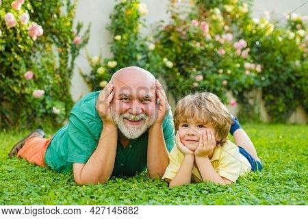 Happy Family Grandson Hugs His Grandpa On Holiday. Grandfather And Grandson Playing - Family Time To