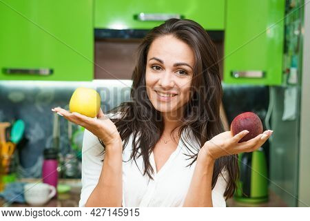 Young Woman Stands In Kitchen Holding Fruits In Her Hands. Caucasian Girl In A Modern Kitchen Holds