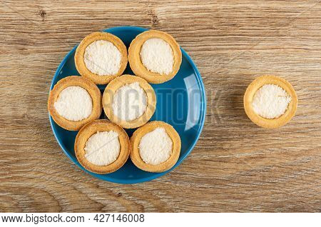 Few Cookies Tartlets With Coconut Shavings In Blue Saucer, Cookie On Brown Wooden Table. Top View