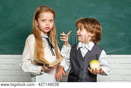 Schoolgirl Helping Pupils Studying At Desks In Classroom. Teacher And Child. Blackboard Background.