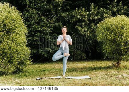 Yoga Training In Nature. Young Woman Meditating On One Leg Doing Asana Pose In The Morning Outdoors.