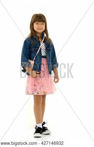 Nice Posing Girl. Full Length Shot Of Stylish Teenage Girl In Denim Jacket, Pink Fluffy Skirt And Sn