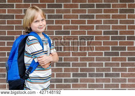 Schoolboy Going To School, Carrying Backpack. Smiling Student Against Brick Wall Of School Building