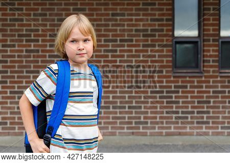 Schoolboy Going To School, Carrying Backpack. Student Against Brick Wall Of School Building With Cop
