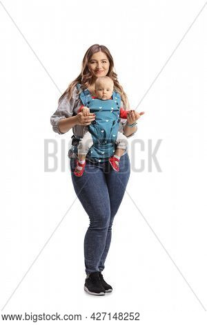 Full length portrait of a mother with a baby in a carrier smiling at camera isolated on white background