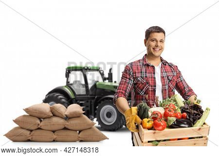 Young farmer with a tractor and pile of sacks holding a crate with vegetables isolated on white background