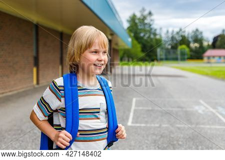 Little Smiling Schoolboy Near School With Backpack. Back To School Concept.
