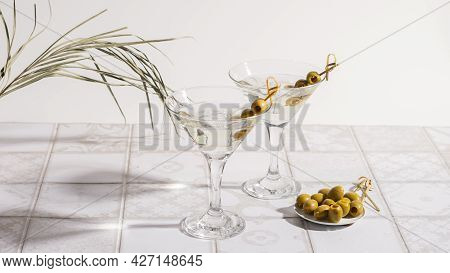 Martini Cocktail With Olives On A Tiled Table. Alcoholic Classic Drink With Ice In An Elegant Glass
