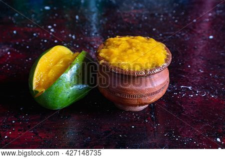 Ripe Mango Pulp In Earthen Bowl With Mango Isolated On Dark Background