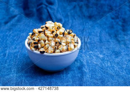 Roasted Maize Or Corn Seeds In A Bowl Isolated On Blue Fabric Background With Copy Space