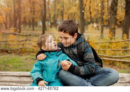 Two Happy Boys In The Woods. Cute Brothers Who Are Smiling Happily Together. Two Brothers Play Outdo