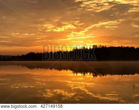Dramatic Orange Sky At Sunset Over Forest Lake Reflecting On Still Water Surface, Forest Line Silhou