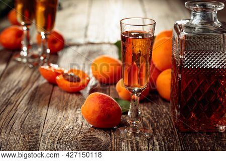 Apricot Liquor And Fresh Apricots On A Old Wooden Table. Wine And Juicy Fruits On A Rustic Backgroun