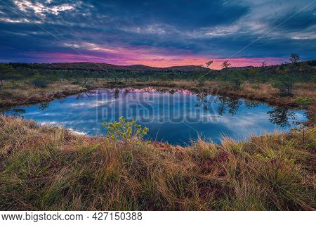 Stunning Autumn Scenery And Small Lake In The Swamp. Spectacular Sunrise Lights And Clouds Reflectio