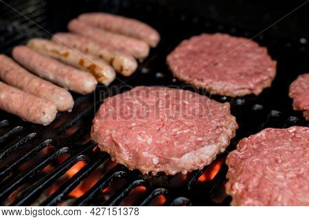 Hamburgers On Grill With Dancing Flames Cooked To Perfection.a Closeup Of Some Fresh And Juicy Hambu