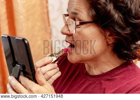 Ukraine, Khmelnytsky, July 2021. An Elderly Woman Paints Her Lips With Lipstick, Taking Care Of Her