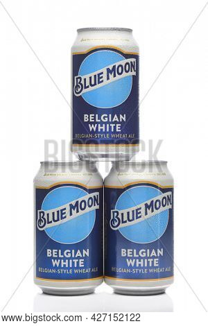 IRIVNE, CALIFORNIA - 17 JUL 2021: Three cold cans of Blue Moon Belgian White Ale with condensation on white.