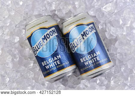 IRIVNE, CALIFORNIA - 17 JUL 2021: Two cans of Blue Moon Belgian White Ale in a bed of Ice.