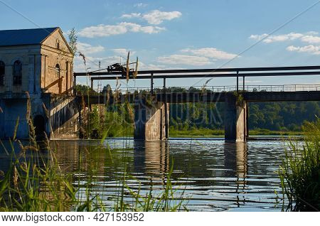 Summer Landscape. An Abandoned Hydroelectric Power Station On The River. View From The River Bank