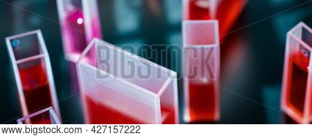 Quartz cuvette for laser chromatography with red liquid. Physical chemistry laboratory