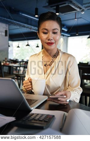 Business Lady In Silk Blouse Working On Laptop At Restaurant Table And Checking Notifications Or Ans