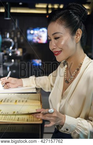Smiling Professional Banquet Manager Reading Restaurant Menu And Taking Notes In Planner