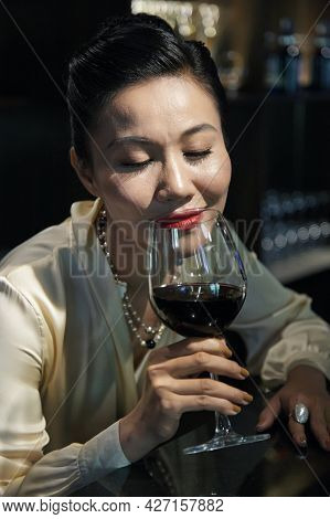Drunk Elegant Woman Enjoying Glass Of Delicious Red Wine At Fancy Restaurant