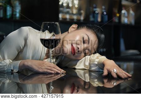 Elegant Woman Fell Asleep At Bar In Restaurant After Drinking Couple Glasses Of Red Wine
