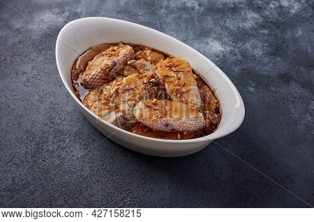 Baked White Sea Fish In A Marinade Of Olive Oil, Rosemary, In White Pan On Dark Textured Background.