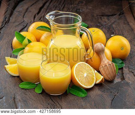 Yellow orange fruits and fresh orange juice isolated on dark wooden background.