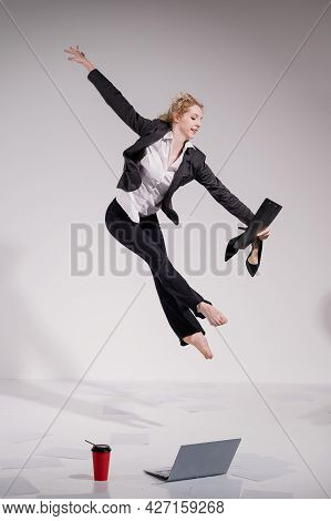 Graceful Barefoot Ballerina In A Business Suit Jumping With Shoes In Her Hands On A White Background