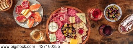 Italian Antipasti Or Spanish Tapas Panorama. Gourmet Cold Meat And Cheese Platter On A Table, Shot F