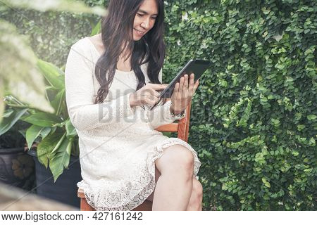Woman\'s Hand Using Phone And Touch Screen At Home. Asian Woman Using Phone And Touch Screen, Happy