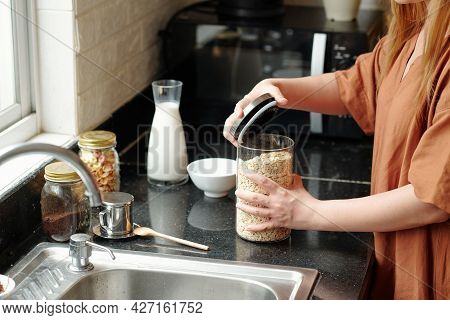 Hands Of Housewife Opening Jar Of Oatmeal Jar When Cooking Breakfast For Her Family