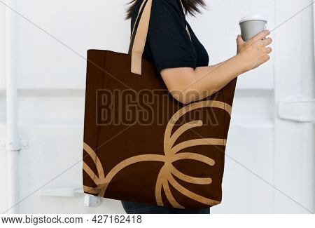 Woman with a brown tote bag side view