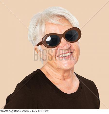 Happy senior woman wearing black oval sunglasses for summer apparel portrait