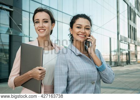 Business, people, tehnology and lifestyle concept: Two business women. One is holding a laptop, the other is talking on the phone. Mixed races. Caucasian woman and African woman.