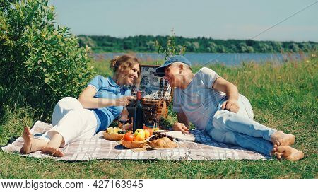 A Happy, Slender Elderly Couple, A Man And A Woman, Are Lying On The Grass In A Park By The River An